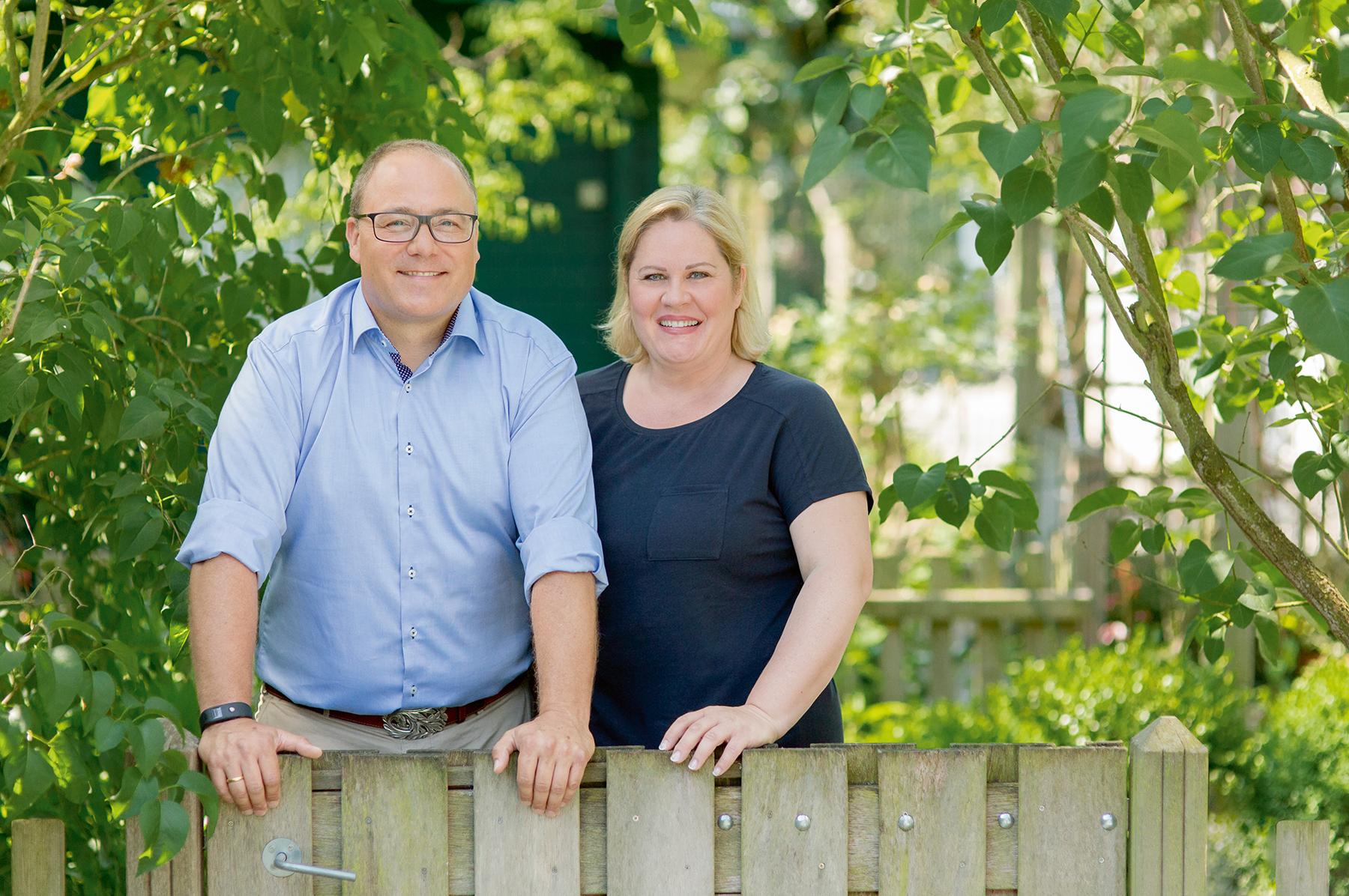 Eheleute Dinger - die Eigentümer von Dinger's Gartencenter Köln - stehen vor einem hölzernen Zaun.